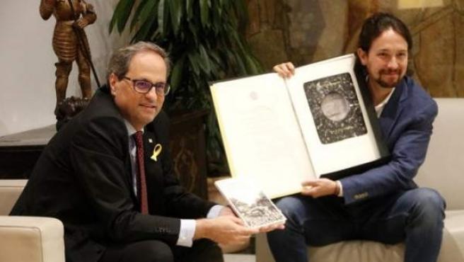 Quim Torra y Pablo Iglesias con el libro y las litografías que se han regalado antes del inicio de la reunión en la Generalitat.