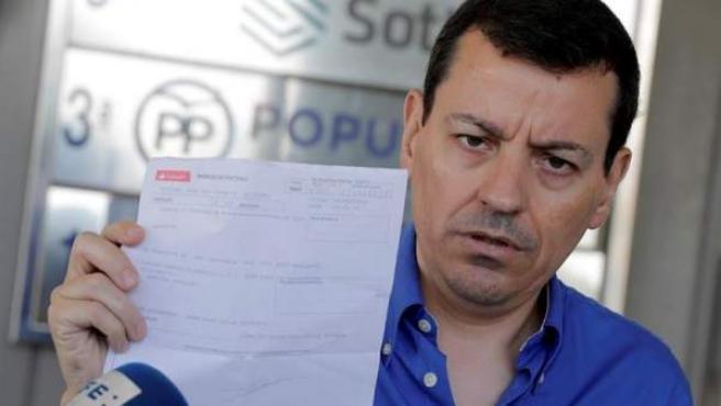 El militante del PP José Luis Bayo muestra el recibo de su pago de la cuota del partido, en la sede del PPCV en Valencia.