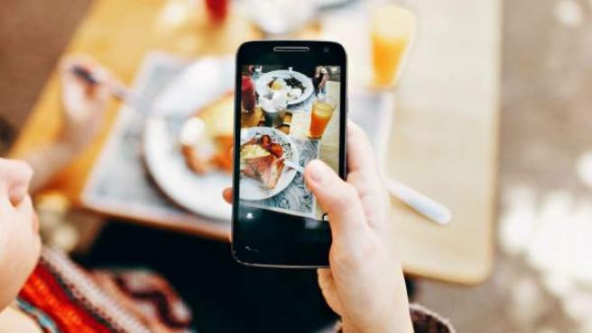 Una chica saca una fotografía con un móvil Samsung.