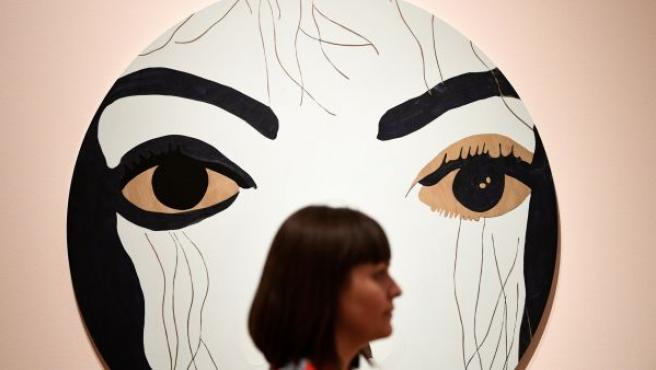 Una mujer pasa delante de la pintura 'Michael', del artista Gary Holmes, durante la presentación a la prensa de la exposición 'Michael Jackson: On the Wall', en la National Portrait Gallery de Londres, (Reino Unido).