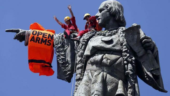 Unos activistas colocan un chaleco salvavidas en el monumento a Colón tras la llegada a Barcelona del Open Arms.