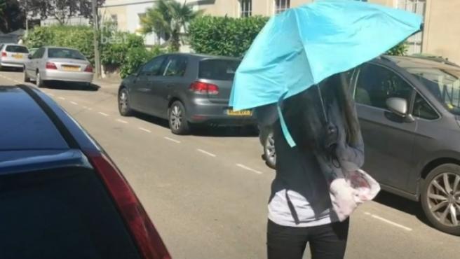 Emma Traynor abre su paraguas para ir del coche a su casa en un día soleado.