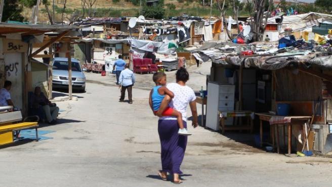 Una mujer con un niño en brazos en el poblado de chabolas de 'El Gallinero', en Madrid