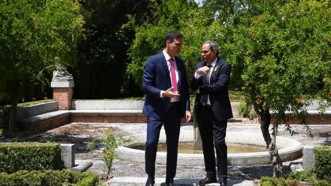 Pedro Sánchez conversa con Quim Torra, mientras dan un paseo por los jardines de la Moncloa.