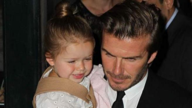 David Beckham sostiene en brazos a su hija Harper.