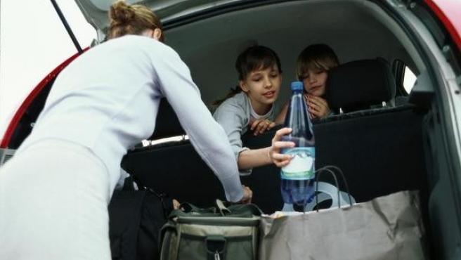 Una familia coloca el equipaje en el maletero de su coche.