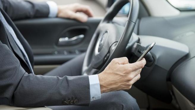 Un hombre utiliza el móvil dentro del coche.