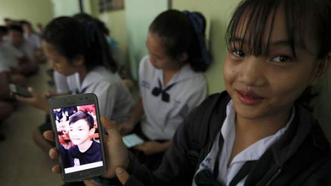 Una estudiante tailandesa muestra una fotografía de su compañero de clase Duangpetch Promthep, quien se encontraba atrapado en la cueva de Chiang Rai.