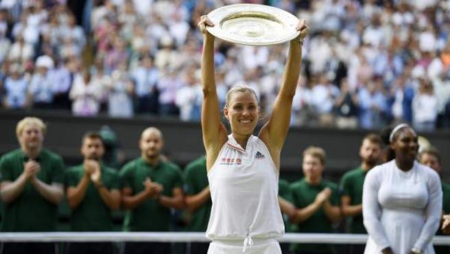 La tenista alemana Angelique Kerber alza su trofeo de ganadora de Roland Garros con Serena Williams al fondo.