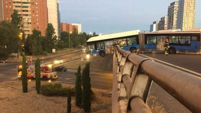 Imagen del bus lanzadera del Mad Cool, suspendido de un puente y siendo retirado con ayuda de una grúa.