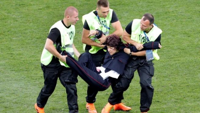 Miembros de seguridad sacan del campo a una espontánea al inicio de la segunda parte del partido Francia-Croacia.