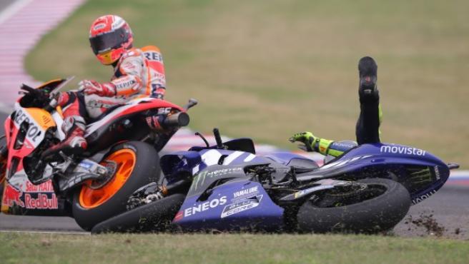 El piloto italiano de MotoGP Valentino Rossi (d), cae al piso en la última curva del circuito tras un toque con el piloto Marc Márquez (i).