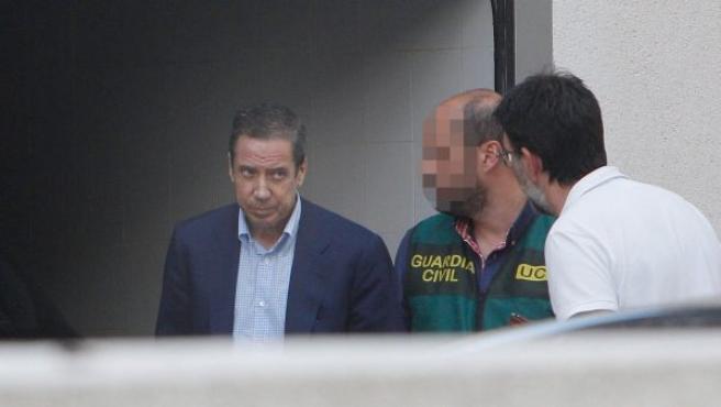 El expresidente de la Generalitat Valenciana y exministro de Trabajo, Eduardo Zaplana, acompañado por agentes de la UCO de la Guardia Civil durante un registro de su chalé de Benidorm.