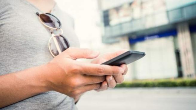 Un hombre usa su smartphone.