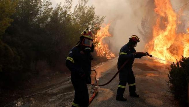Bomberos tratan de extinguir un incendio en Grecia.