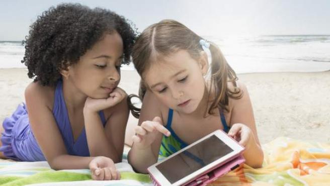 Dos niñas con una tablet en la playa.
