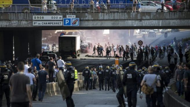 Varios taxistas franceses se enfrentan a la policía antidisturbios mientras intentan interrumpir el tráfico en hora punta en una carretera de circunvalación en París (Francia).