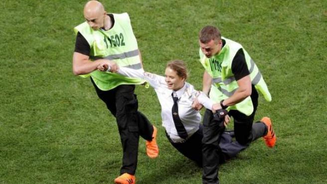 Miembros del personal de seguridad reducen a una integrante de Pussy Riot durante la final del Mundial de Fútbol de Rusia 2018.