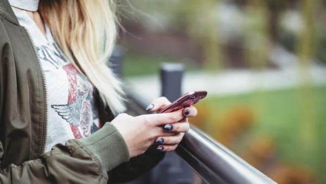 Una mujer con su teléfono móvil, en una imagen de archivo.