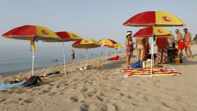 Varias sombrillas con los colores de la bandera de España en la playa de Arenys de Mar.