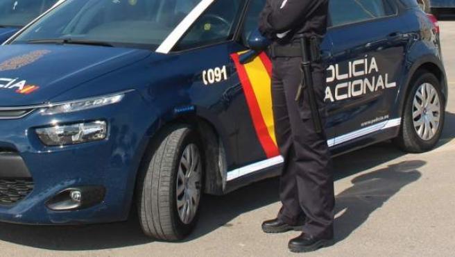 Imagen de archivo de un agente y un coche de Policía.