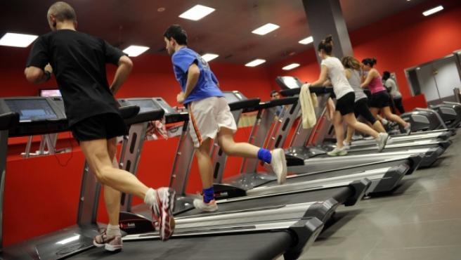 Varias personas haciendo ejercicio en un gimnasio.