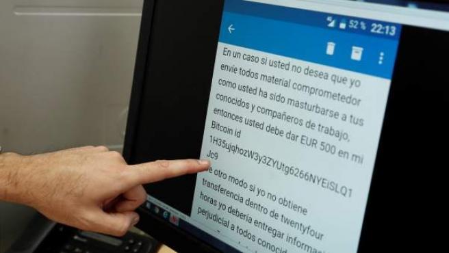 Un agente de Policía señala en una pantalla un mensaje de intento de extorsión en internet.
