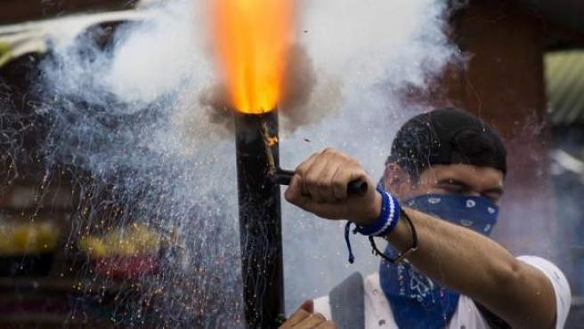 Un joven dispara un mortero durante una multitudinaria marcha en apoyo a los estudiantes nicaragüenses y en rechazo al presidente Daniel Ortega, el 23 de julio de 2018, en Managua (Nicaragua).