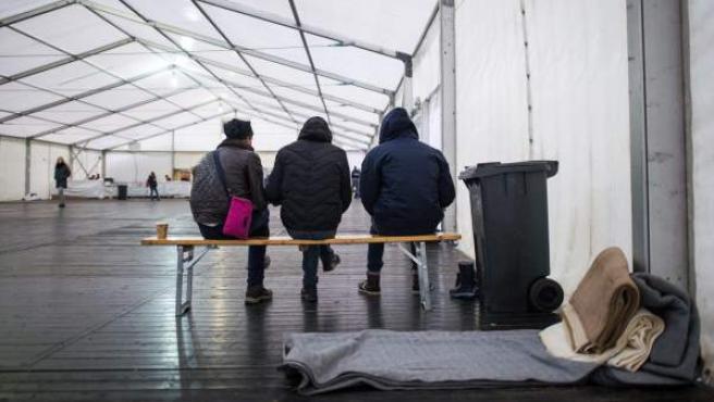 Varios refugiados afganos esperan para registrarse en un campamento temporal alemán para solicitar asilo en Suecia o Dinamarca.