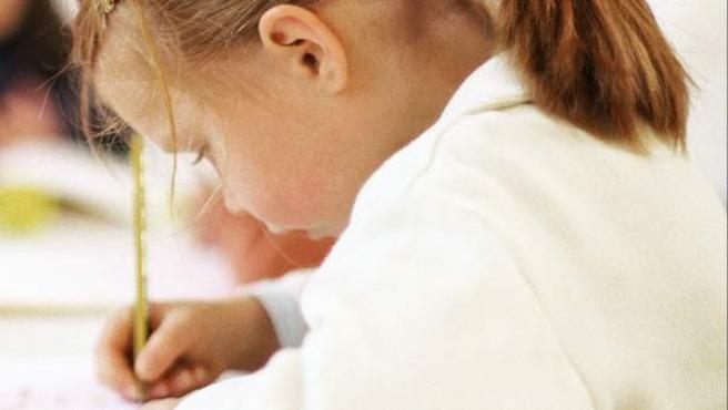 Una niña escribiendo en el colegio.