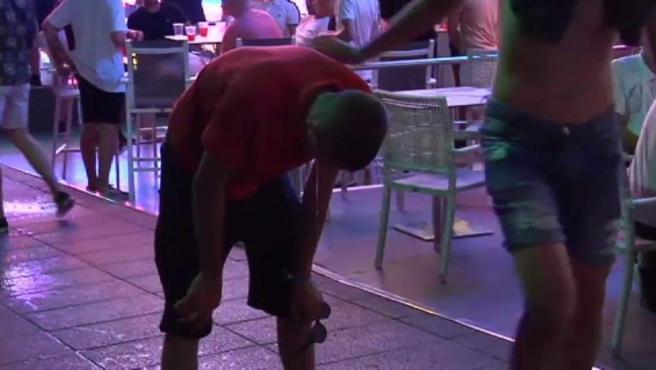 Un turista vomita en una calle de Magaluf.