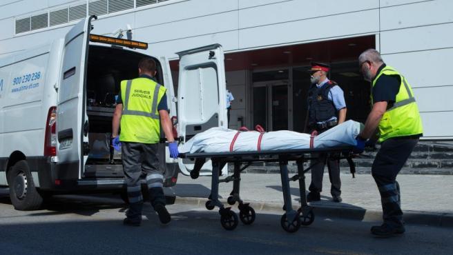Miembros del servicio judicial retiran el cadáver del hombre que ha sido abatido al intentar acceder a la comisaría de los Mossos de Cornellà con un cuchillo.