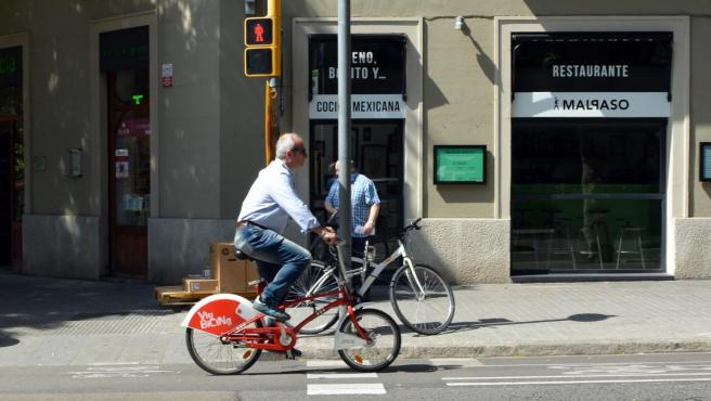 Un hombre circulando en bicicleta por Barcelona.