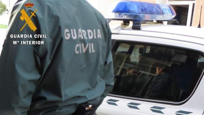 Un agente de la Guardia Civil, al lado de un coche.
