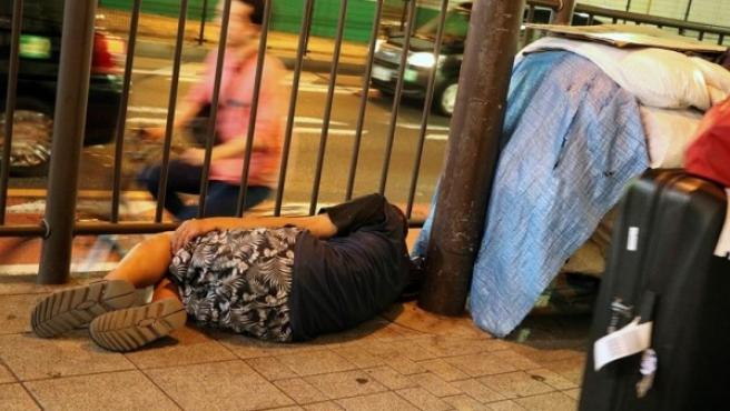 Personas sin hogar duermen en las calles del bullicioso distrito de Shinjuku, en Tokio.