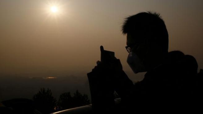 Un joven usa una mascarilla mientras hace una foto en Pekín (China).
