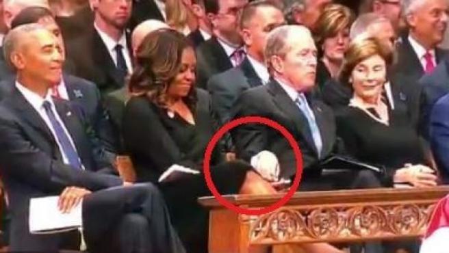 Momento en el que George Bush pasa un acaramelo a Michelle Obama en el funeral de John McCain.