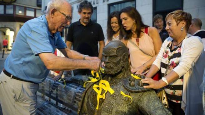 Militantes de Eusko Alkartasuna colocan lazos amarillos en la escultura Reflexión, en en Vitoria.