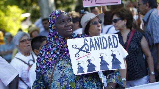 Una mujer inmigrante sostiene una pancarta contra los recortes en la novena 'marea blanca' por la sanidad pública en Madrid.