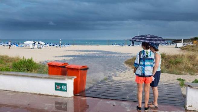 <p>Dos mujeres se resguardan de la lluvia bajo un paraguas en la playa de Punta Prima, en el municipio de Sant Lluís (Menorca).</p>