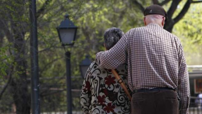 Una pareja de ancianos pasea por un parque.