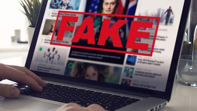"""La palabra """"fake"""" (falso) sobre la pantalla de un portátil en la que se ven noticias."""