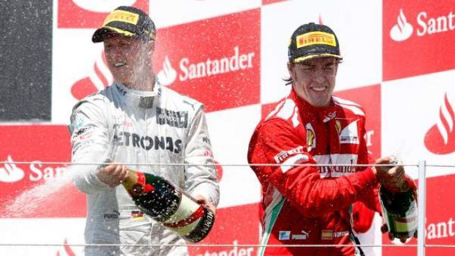 El piloto de Fórmula 1 Fernando Alonso celebra su victoria junto Michael Schumacher, que quedó tercero, en el GP de Europa celebrado en junio de 2012