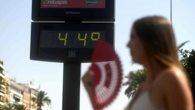 Una joven se abanica ante un termómetro que marca 44ºC debido a la ola de calor.