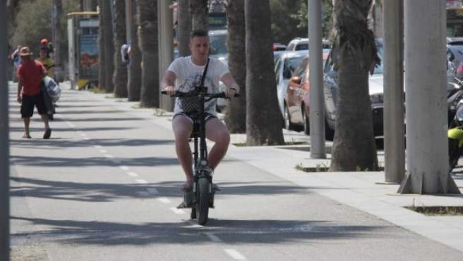 Un hombre circulando por Barcelona en patinete eléctrico.