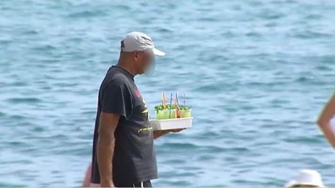 Un hombre vende mojitos en una playa.