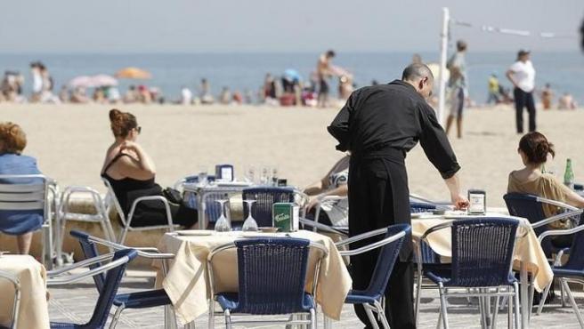 Un camarero atiende las mesas de un restaurante junto a la playa.