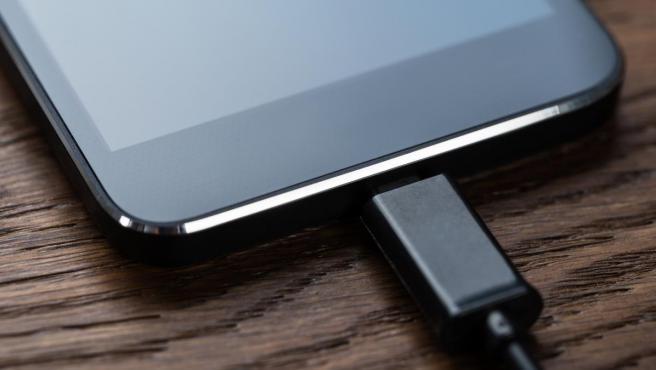 Detalle de un teléfono móvil cargando su batería.