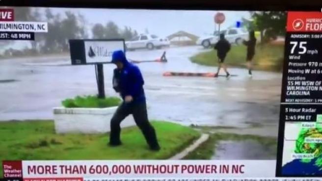 Momento en el que el reportero Mike Seidel finge que le cuesta caminar ante el viento huracanado, mientras dos transeúntes pasean tranquilos al fondo.