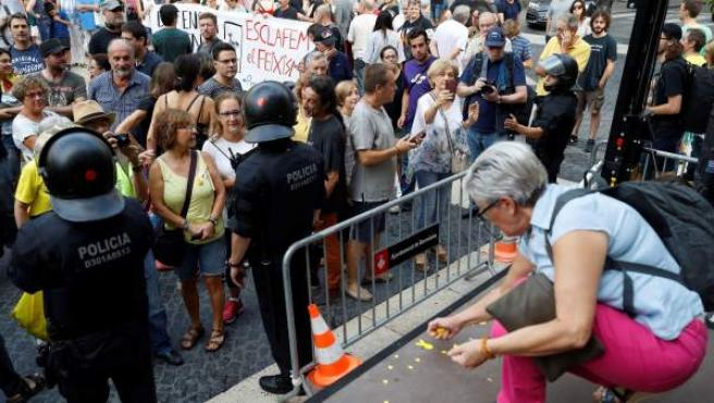 Una mujer de la asociación Hablamos Español retira lazos amarillos del escenario donde iban a intervenir y arrojados por grupos independentistas.